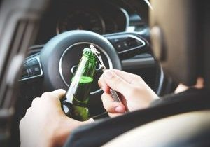 image of driver opening beer bottle