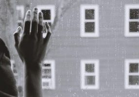 image of person indoors with hand on window